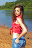 Den sexiga härliga flickan med långt anseende för mörkt hår i grov bomullstvill kortsluter på stranden nära vattnet på en solig d Royaltyfri Foto