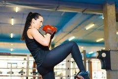 Den sexiga idrotts- flickan g?r en spark in idrottshallen kvinnan i boxninghandskar utbildar kn?et arkivbild