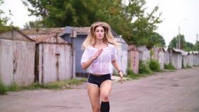 Den sexiga idrotts- unga blonda kvinnan i kortslutningar, utför olika styrkaövningar med hjälpen av gummihjul, hopp I sommar stock video