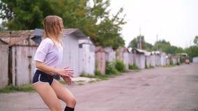 Den sexiga idrotts- unga blonda kvinnan i kortslutningar, utför olika styrkaövningar med hjälpen av gummihjul, hopp I sommar arkivfilmer
