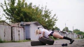 Den sexiga idrotts- unga blonda kvinnan i kortslutningar, utför olika styrkaövningar med hjälpen av gummihjul, push-UPS, in lager videofilmer