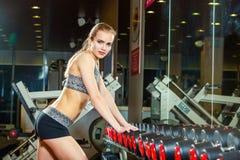 Den sexiga idrottsman nen med a i idrottshallen lutar på hantel Arkivbild