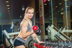 Den sexiga idrottsman nen med a i idrottshallen lutar på hantel Royaltyfria Bilder