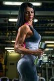 Den sexiga konditionbrunettkvinnan gör bicepskrullning med hantlar i idrottshallen royaltyfri foto