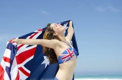 Den sexiga kvinnaaustralier sjunker på stranden Fotografering för Bildbyråer