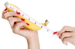 Den sexiga kvinnahanden med rött spikar hållande och att mäta bananen Arkivfoto