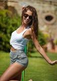 Den sexiga kvinnan bevattnar en trädgård arkivfoton