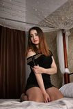 Den sexiga kvinnan i aftonklänning sitter på sängen och lägger den kala skuldran Royaltyfria Foton