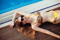 Den sexiga kvinnan i bikini som tycker om sommarsolen och garvar under ferier nära, slår samman Top beskådar pool simningkvinnan  royaltyfri bild