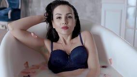 Den sexiga kvinnan i brunnsortsalong tar ett bad som fylls med, mjölkar och dekorerat med blommor arkivfilmer