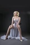 Den sexiga kvinnan i den vita modeklänningen sitter på stol Royaltyfria Foton