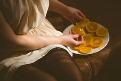 Den sexiga kvinnan i en svart damunderkläder på soffan äter apelsiner Kvinnan äter nya apelsiner på den vita plattan Arkivfoto