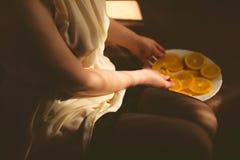 Den sexiga kvinnan i en svart damunderkläder på soffan äter apelsiner Kvinnan äter nya apelsiner på den vita plattan Fotografering för Bildbyråer