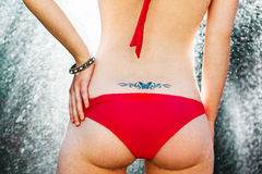 Den sexiga kvinnan med blänker tatueringen på baksida Arkivfoton
