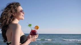Den sexiga kvinnan med lockigt hår dricker den färgrika coctailen, stående av att le flickan på stranden, skinande havsbakgrund, stock video