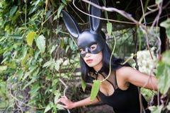den sexiga kvinnan med den svarta klänningen och kaninen gå i ax Arkivfoto