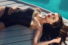 Den sexiga kvinnan sunning vid simbassängen har gyckel på strandpartiet Arkivfoto