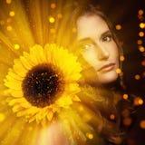 Den sexiga kvinnan visar hennes naturliga blick med en solros royaltyfri bild