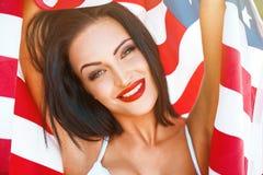 Den sexiga kvinnaståenden med USA sjunker i solnedgång Royaltyfria Bilder