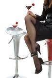 Den sexiga kvinnlign lägger benen på ryggen i höga häl på coctailstången Arkivbilder