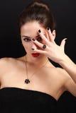 Den sexiga makeupkvinnan som visar hennes svart, spikar arkivbild