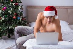 Den sexiga mannen i sängen som bär den santa hatten i julbegrepp Royaltyfri Fotografi