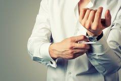 Den sexiga mannen knäppas manschettknappen på franska manschetter Royaltyfri Bild