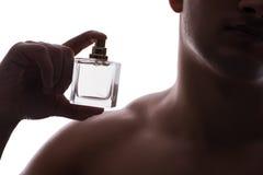 Den sexiga mannen med flaskan av doft Arkivbild
