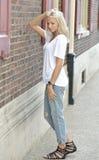 Den sexiga modellen poserar i den vit t-skjortan och jeans - stad Royaltyfri Bild