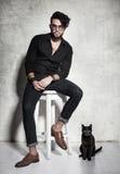 Den sexiga modemanmodellen klädde tillfälligt posera med en katt mot grungeväggen Arkivfoto