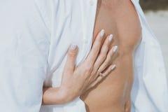 Den sexiga muskulösa nakna mannen och kvinnliga händer knäpper upp hans jeans Royaltyfri Bild