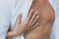 Den sexiga muskulösa nakna mannen och kvinnliga händer knäpper upp hans jeans Fotografering för Bildbyråer
