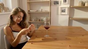 Den sexiga och attraktiva kvinnan i frank klänning sitter på tabellen i ett kafé med exponeringsglas av rött vin och att smsa på  arkivfilmer