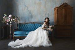 Den sexiga och härliga brunettmodellflickan i stilfullt och trendigt snör åt bröllopsklänningen med nakna skuldror sitter på den  royaltyfria foton