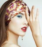 Den sexiga skönhetflickan med röda kanter och spikar Provokativt smink Lyxig kvinna med blåa ögon Modebrunettstående Arkivfoto