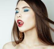 Den sexiga skönhetflickan med röda kanter och spikar Provokativt smink Lyxig kvinna med blåa ögon Modebrunettstående Arkivfoton