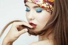 Den sexiga skönhetflickan med röda kanter och spikar Provokativt smink Lyxig kvinna med blåa ögon Modebrunettstående Arkivbilder