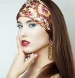 Den sexiga skönhetflickan med röda kanter och spikar Provokativt smink Lyxig kvinna med blåa ögon Modebrunettstående Arkivbild