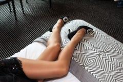 Den sexiga slanka kvinnan lägger benen på ryggen i skor för hög häl arkivfoto