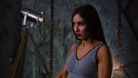 Den sexiga sportiga flickan i korta kortslutningar och blåst upp press med hantlar på bakgrunden av en stengrå färgvägg lyfter in lager videofilmer