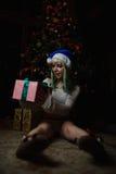 Den sexiga unga flickan har mottagit gåvan under julgranen Arkivfoto