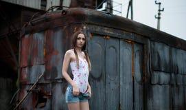 Den sexiga unga flickan klär av på en bakgrund av att få-tillsammans i stilen av stolpe-apokalypens Royaltyfri Bild
