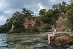 Den sexiga unga härliga flickan i bikinin som sitter på, vaggar på stranden royaltyfri bild