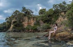 Den sexiga unga härliga flickan i bikinin som sitter på, vaggar på den tropiska stranden royaltyfria bilder