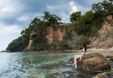 Den sexiga unga härliga kvinnan i bikinin som sitter på, vaggar på stranden royaltyfri foto