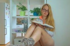 Den sexiga unga härliga kvinnan i exponeringsglas som sitter och, läser boken arkivfoto