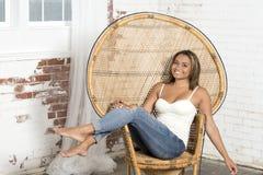 Den sexiga unga kvinnan i den vit behållaren och jeans kopplar av Royaltyfri Foto