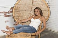 Den sexiga unga kvinnan i den vit behållaren och jeans kopplar av Royaltyfria Foton