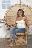 Den sexiga unga kvinnan i den vit behållaren och jeans kopplar av Royaltyfri Fotografi