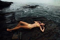 Den sexiga unga kvinnan ligger på en vaggahavkust Härlig flicka på stenig bakgrund Arkivfoton
